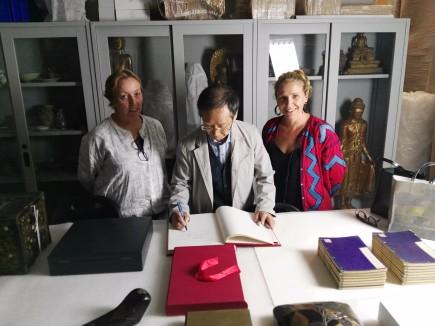 Hiromu Ozawa firmando el libro de oro del Museo junto a Carmela Gallego y Nerea Díez de Pinos